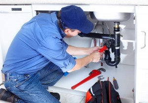 a plumber crouched down as he repairs a sink's drain trap